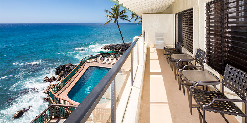 View of ocean and pool from lanai at Poipu Shores Resort